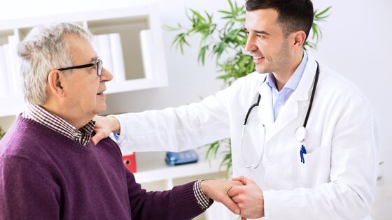Young doctor senior patient shaking hands