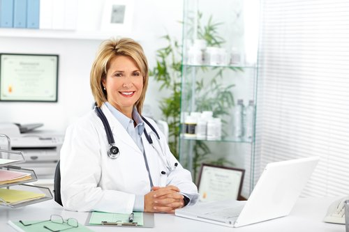 Smiling female doctor in front of computer