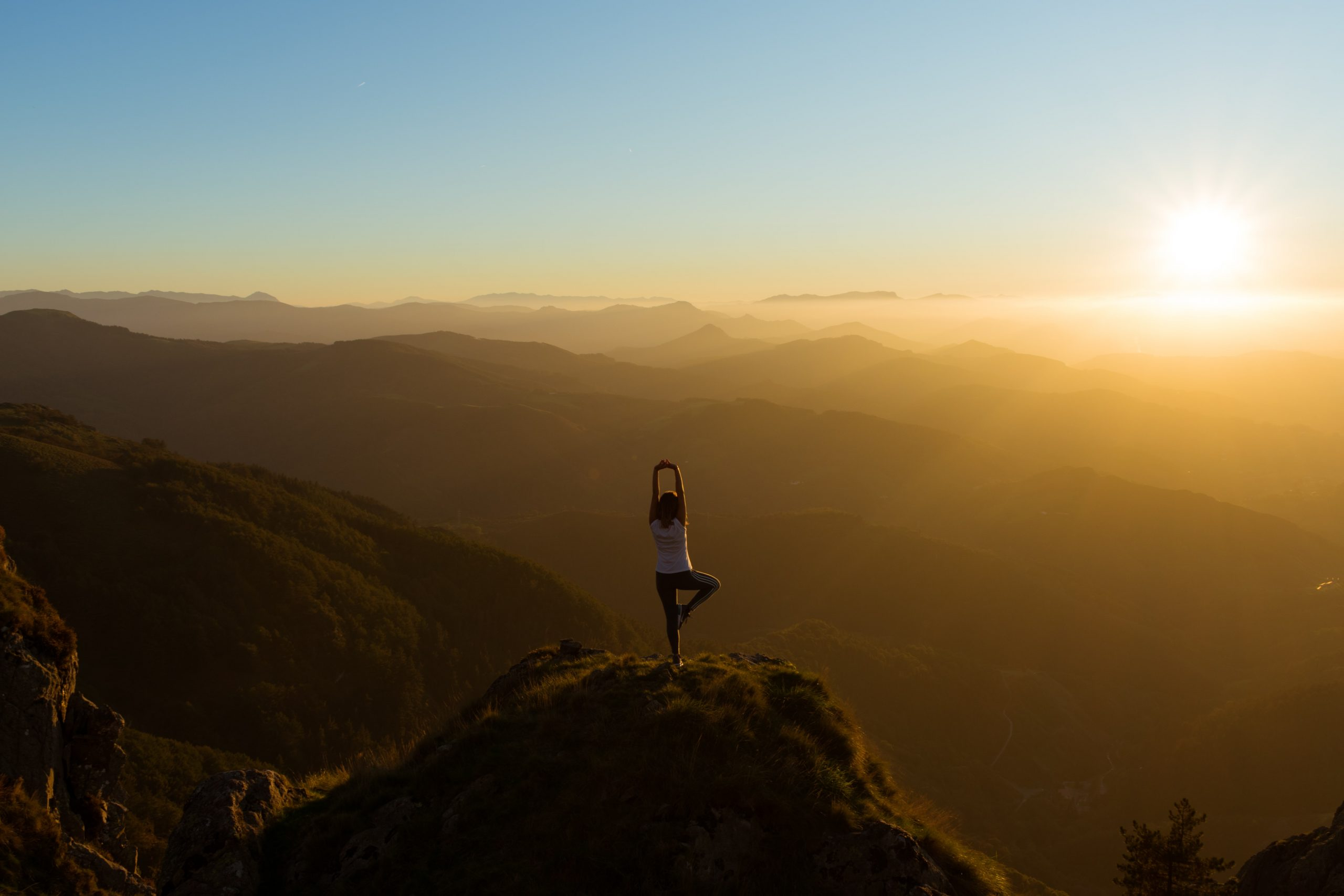 Young woman doing yoga exercises outdoors on the background of mountains at sunset
