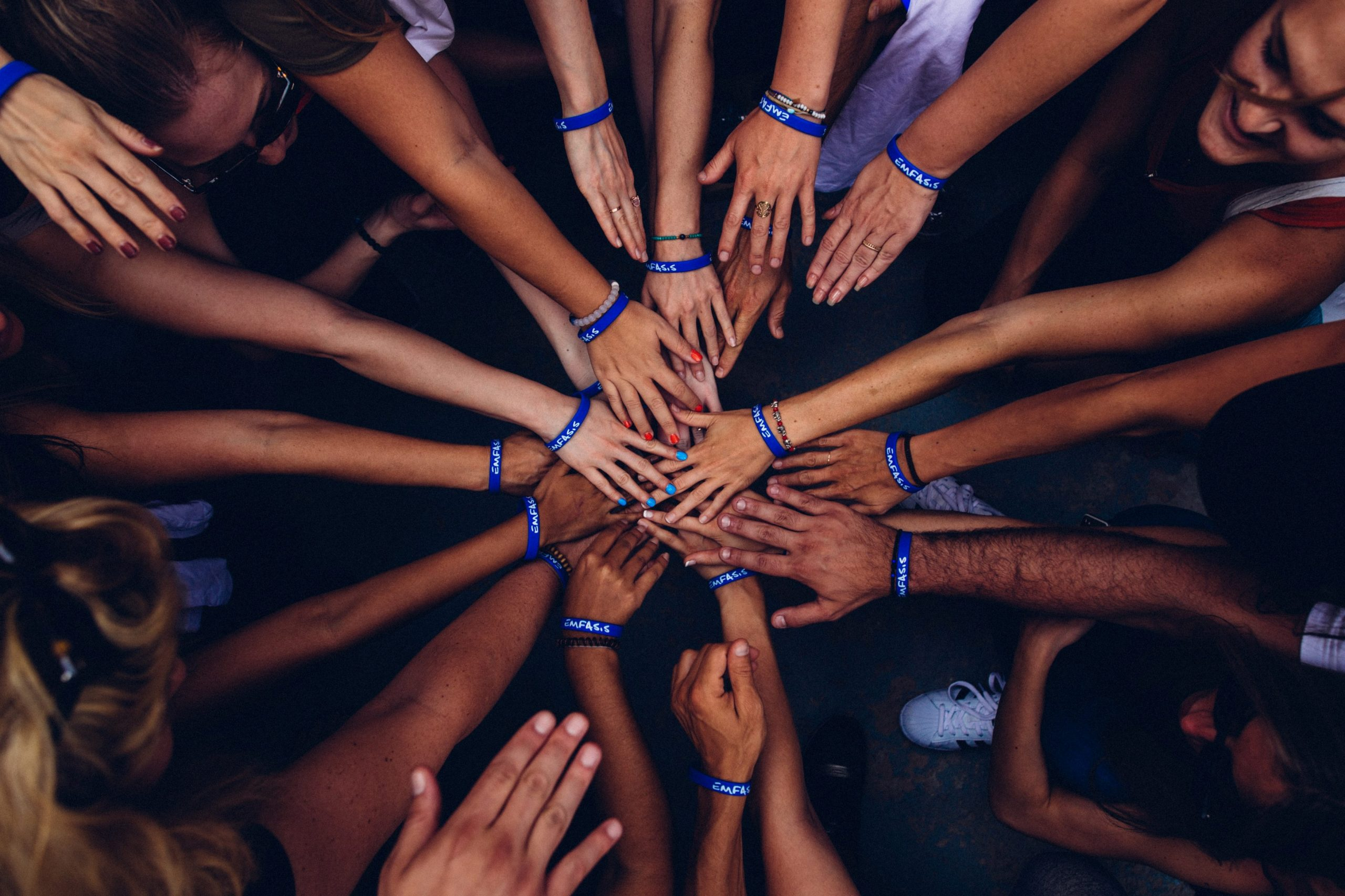 People stand in a circle and reach out with their hands to each other